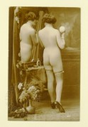 Naked model posing with a mirror