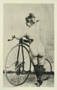 Naked model posing with a bike